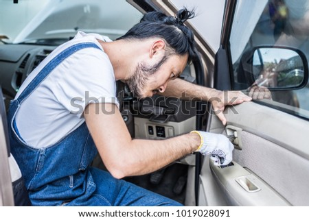 Fixing car engine in automobile repair garage. Handsome mechanics in uniform are repairing car while working in auto service #1019028091