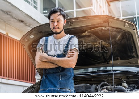 Fixing car engine in automobile repair garage. Handsome mechanics in uniform are repairing car while working in auto service #1140445922