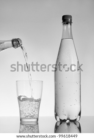 Fizzy drink poured into glass black and white studio shot - stock photo
