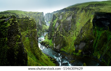 Fjadrargljufur valley in Iceland, shown here on a rainy and breezy day.  The cloud layer was thin, allowing the sunlight to shine through and make the mossy cliffs pop with color.