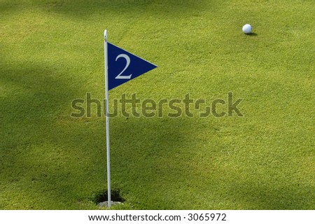 flag and ball in a green golf field