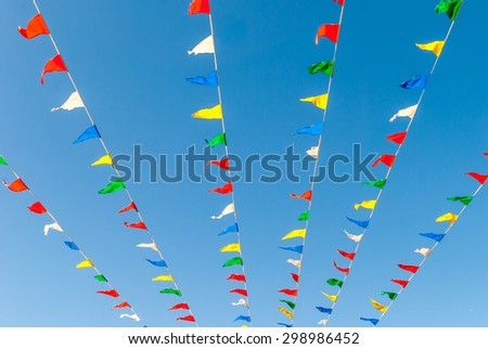 Flag banners blowing in wind. Flapping flags. Streamer flags. Abstract flag colors. Pennant flag strings. Color pennants. Abstract design art. Urban geometry.