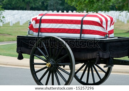 Flag draped casket on caisson being pulled to grave site in Arlington National Cemetery with grave stones in background