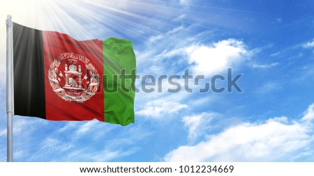 Flag of Afghanistan on flagpole against the blue sky