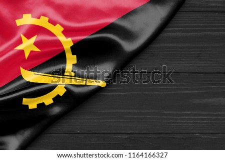 Flag of Angola and place for text on a dark wooden background #1164166327