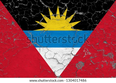 Flag of Antigua and Barbuda painted on cracked dirty wall. National pattern on vintage style surface.