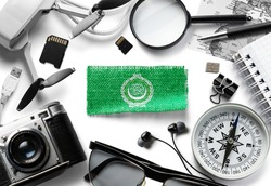 Flag of Arab League and travel accessories on a white background.