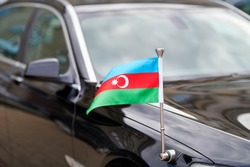 Flag of Azerbaijan at the diplomatic black car. Diplomat of Azerbaijan. Azerbaijan flag waving on ambassador's car. Tricolour, with a white crescent and an eight-pointed star in the center