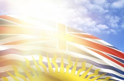 flag of British Columbia against the blue sky with sun rays