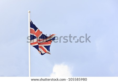 Flag of British waving on top of a pole with light blue sky.
