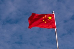 flag of China on clouds blue sky background