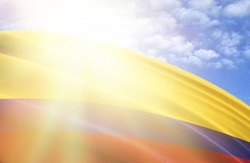 flag of Colombia against the blue sky with sun rays