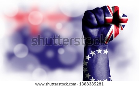Flag of Cook Islands painted on male fist, strength,power,concept of conflict. On a blurred background with a good place for your text. #1388385281