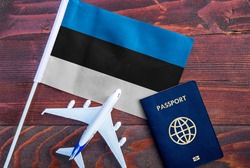 Flag of Estonia with passport and toy airplane on wooden background. Flight travel concept.