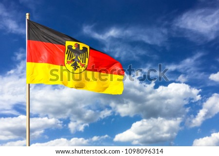 Flag of Germany (Federal Republic of Germany; in German: Bundesrepublik Deutschland) waving in the wind on a bright sunny summer day and blue sky background.