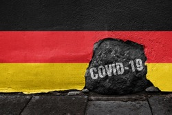 Flag of Germany on the wall with cracked stone with Coronavirus name on it. 2019 - 2020 Novel Coronavirus (2019-nCoV) concept, for an outbreak occurs in Germany.
