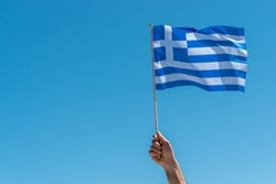 Flag of Greece in human hand on sky background.