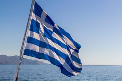 Flag of Greece on a cruise ship against greek coastline