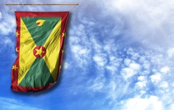 Flag of Grenada. Vertical flag, against blue sky with place for your text