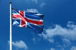 Flag of Iceland on a high flagpole. Waving Icelandic Flag Against a Blue Sky with Clouds. National Flag of Iceland. Image for Icelandic Republic Day, National Day