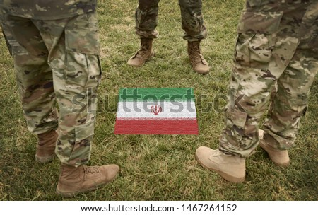 Flag of Iran on the grass. Soldiers legs in green camouflage military uniform (collage).