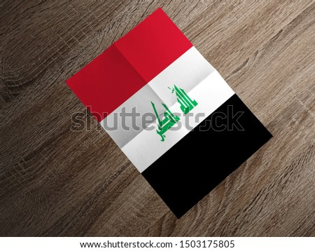 Flag of Iraq on paper. Iraq Flag on wooden table.
