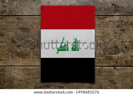 Flag of Iraq on wooden board. Paper Flag of Iraq on wooden table.