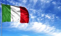 Flag of Italy on flagpole against the blue sky