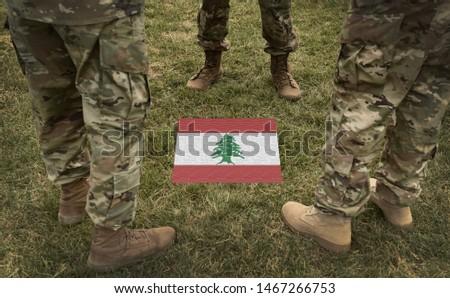 Flag of Lebanon and soldiers legs in green camouflage military uniform (collage).