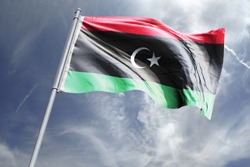 Flag of Libya in the sky. National Flag of Libya on flag pole for Independence day.