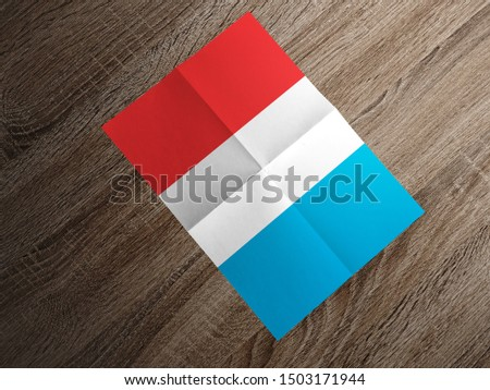 Flag of Luxembourg on paper. Luxembourg Flag on wooden table. #1503171944