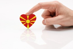 Flag of Macedonia. Love and respect Macedonia. A man's hand holds a heart in the shape of the Macedonian flag on a white glass surface. The concept of Macedonian patriotism and pride.