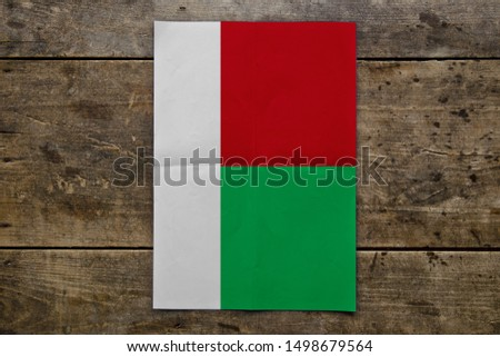 Flag of Madagascar on wooden board. Paper Flag of Madagascar on wooden table.