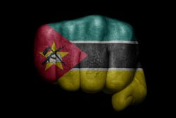 Flag of Mozambique painted on strong fist on black background