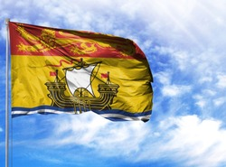Flag of New Brunswick on flagpole against the blue sky