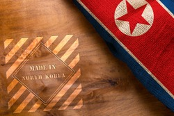 Flag of North Korea made from rough fabric on a wooden background and stamp made in North Korea