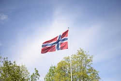Flag of Norway against the blue sky of clouds and trees.