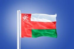 Flag of Oman flying against a blue sky.