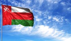 Flag of Oman on flagpole against the blue sky