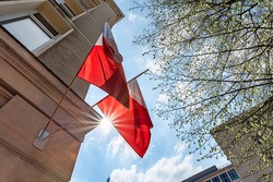 Flag of Poland on facade of a building waving in the wind with sun rays. Celebrating Polish National Flag Day