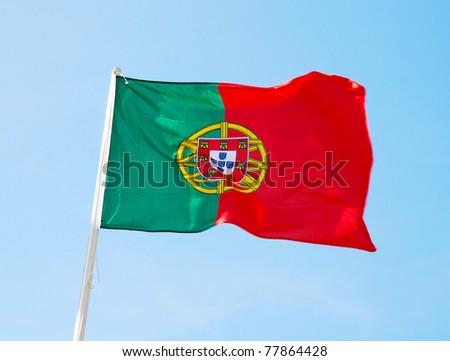 Flag of Portugal waving, against blue sky