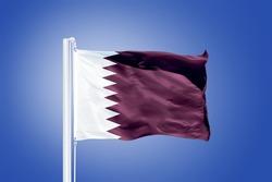 Flag of Qatar flying against a blue sky.