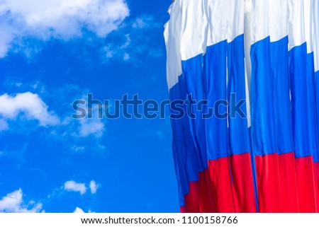 Flag of Russia. Flag of the Russian Federation against the blue sky. Red blue white flag. #1100158766