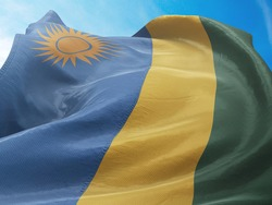Flag of Rwanda on Flag Pole in Blue Sky. Rwanda Flag for advertising, celebration, achievement, festival, election. The symbol of the state on wavy cotton fabric.