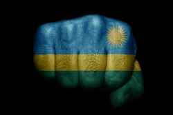 Flag of Rwanda painted on strong fist on black background