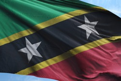 Flag of Saint Kitts and Nevis fabric waving in the blue sky. National Flag of Saint Kitts and Nevis for Independence day.