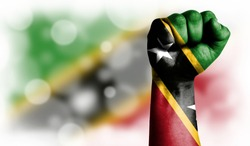 Flag of Saint Kitts and Nevis painted on male fist, strength,power,concept of conflict. On a blurred background with a good place for your text.
