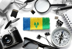 Flag of Saint Vincent and travel accessories on a white background.
