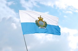 Flag of San Marino in front of blue sky