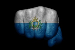 Flag of San Marino painted on strong fist on black background